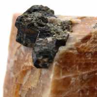 Zwarte micakristallen op oranje calcietblok